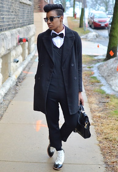 Sushanna M. - Sunglass.La Gold Gilded Horn Rimmed Sunglasses, Black Double Breasted Coat, Men's Black Bow Tie, Black Cropped Overalls Jumpsuit, Gold Gilded Black Satchel, Black & White Wingtip Ankle Booties - Under Wraps