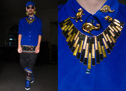 Andre Judd - Bright Blue Baseball Cap, Uniqlo Bright Blue Shirt, Gold Ray Neckpiece, Collection Of Vintage Dinosaur Brooches, H.Custodio Gold Disc Earrings, M Barretto Ethnic Print Trousers With Triangular Overlapping Panel, Vintage 70s Gold Frames - The Emperor's New Groove
