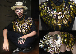 Andre Judd - Gold Feather Printed Knit Sweater, Chainmail Neckpiece With Insects And Crystals, Insect Rings, Woven Hat, Chunks Of Cross Earrings - FEATHERS AND INSECTS - FARMPUNK