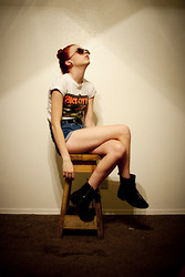 Zoe C - Local Artist Distressed Graphic Tee, Mid Rise Denim Shorts, Boots, Thrifted Vintage Glasses - Budz from space