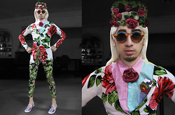 Andre Judd - Rose Brooch, Rose Headpiece, Rose Knit Cardigan, Floral Trousers, Round Frames, Aztec Print Slip Ons - KINGDOM OF THE ROSE
