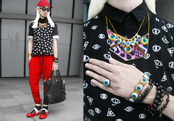 Andre Judd - Trf Eye Print Tank Layered Over Black Button Down Shirt, Trf Patterned Print Trousers, Kiroic Tech Bybrid Boots, House Of J Eyeball Neckpiece, Eyeball Necklace, Cakes And Troubles Eyeball Ring, Angular Visor Cap, Round Frames, Prada Tote, House Of J Eyeball Bracelet - EYE SEE RED
