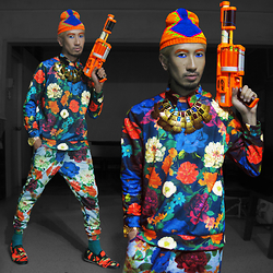 Andre Judd - Floral Sweater, Floral Heather Track Pants, Camo Slipons, Toygun, Bejewelled Neckpiece, Floral Button Down Shirt, Striped Socks - FLOWER POWER