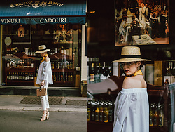 Andreea Birsan - White Off Shoulder Top, White Jeans, Embroidered Strappy Sandals, Square Straw Bag, Neck Scarf, Straw Boater Hat, Clear Lens Glasses - The Parisian white summer outfit you will want to try