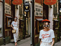 Andreea Birsan - Red Beret, White Oval Sunglasses, Printed T Shirt, White High Waisted Peg Trousers, Mini Straw Bag, Red Pearl Embellished Strappy Sandals - Here's a chic and fresh way to styling your old tee