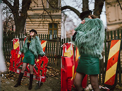Andreea Birsan - Green Faux Fur Coat, Green Leather A Line Mini Skirt, Fishnet Stockings, Baker Boy Hat, Glasses, Black Knee High Boots - The return of the knee high boots