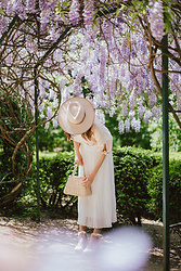 Andreea Birsan - Beige Fedora Hat, Beige Linen Short Sleeve Shirt, Straw Bag, White Midi Pleated Skirt, Beige Tie Detail Wedges - Feminine summer outfit
